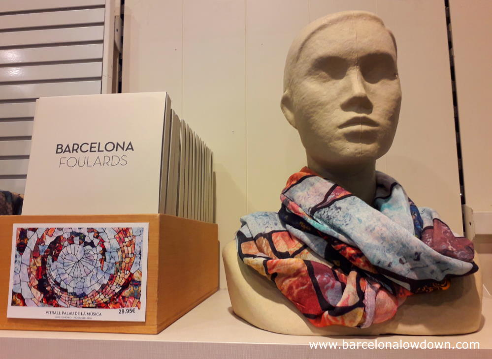 A shops dummy with a colourful ladies scarf inspired by the Catalan musica palace