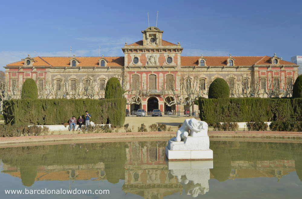 Photo of the Catalan Parliament building in Barcelona citadel park. Ther is a small pond in front of the building with a white marble statue of a crying girl.