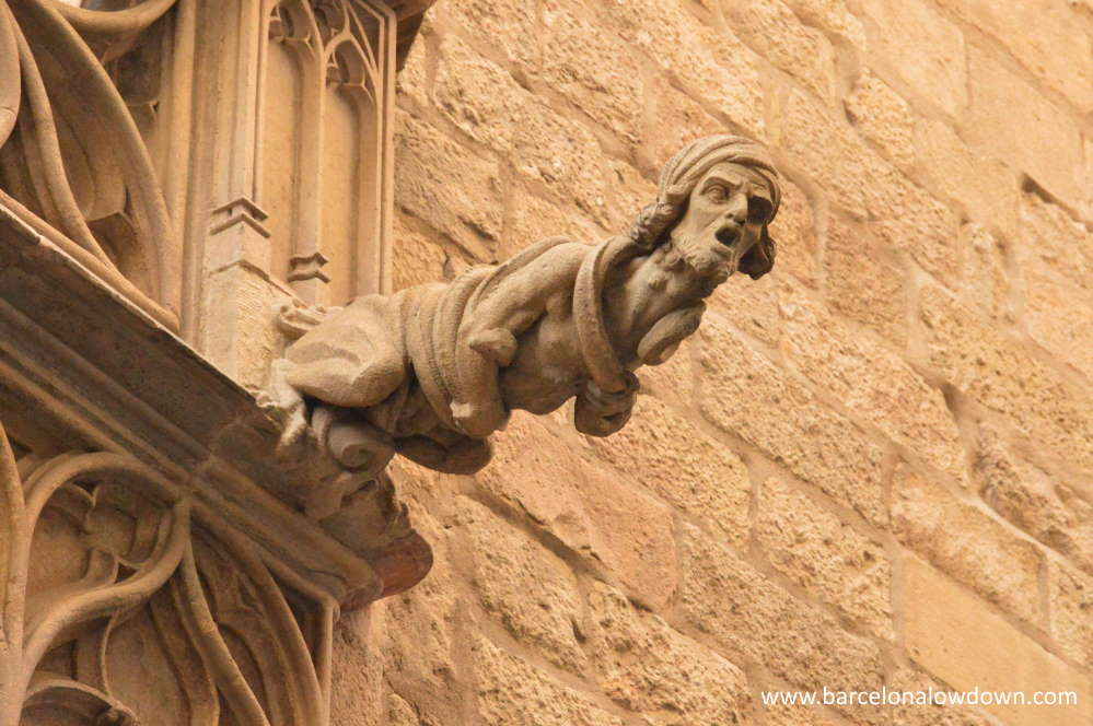 Stone gargoyle on the side of an old building in the Gothic Quarter of Barceona
