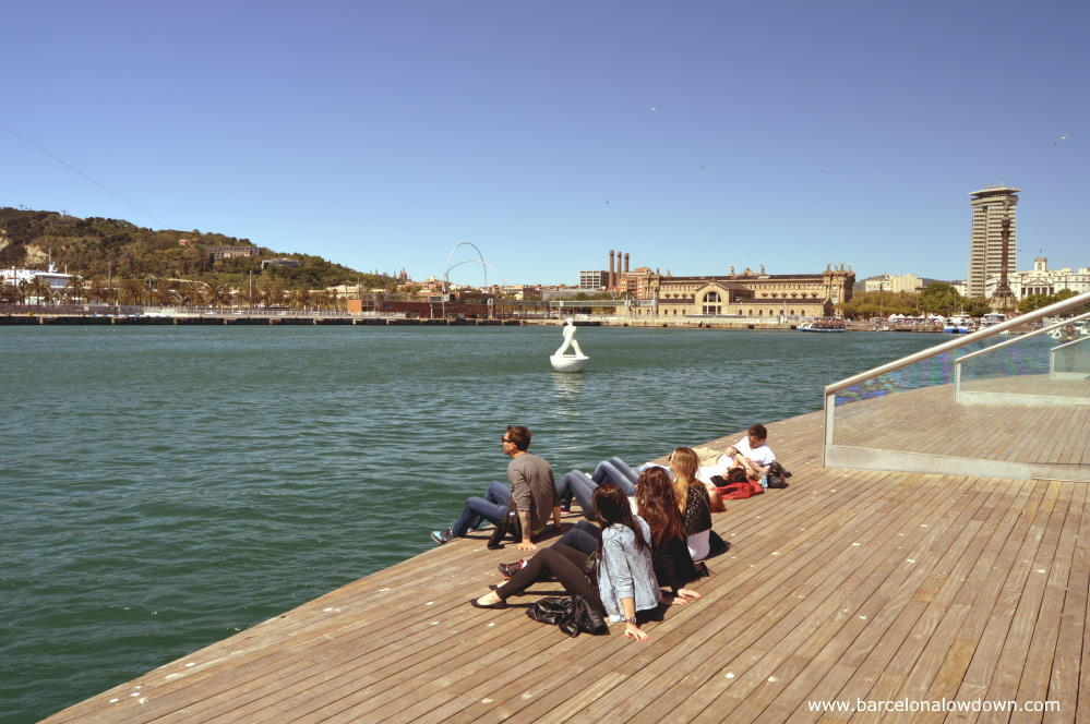 Tourists sitting on the Rambla del Mar boardwalk in Barcelona Harbour