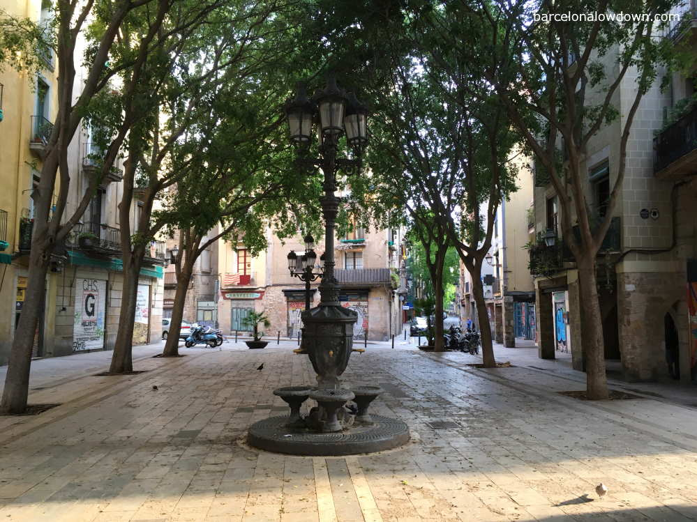 A pretty tree lined plaza with a cast iron water fountain in Barcelonas el Born neighbourhood.