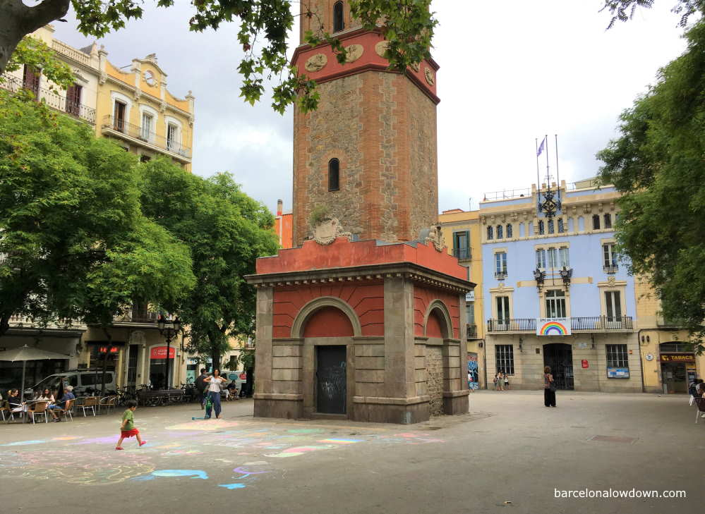 A child and his mother playing in front of the clock tower in the Plaça de la Vila de Gràcia, Barcelona