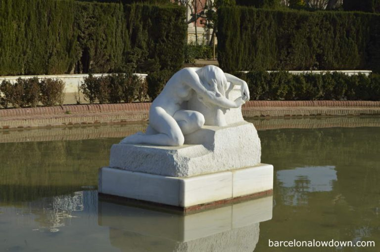 Desolation - A white marble statue of a weeping woman in a pond