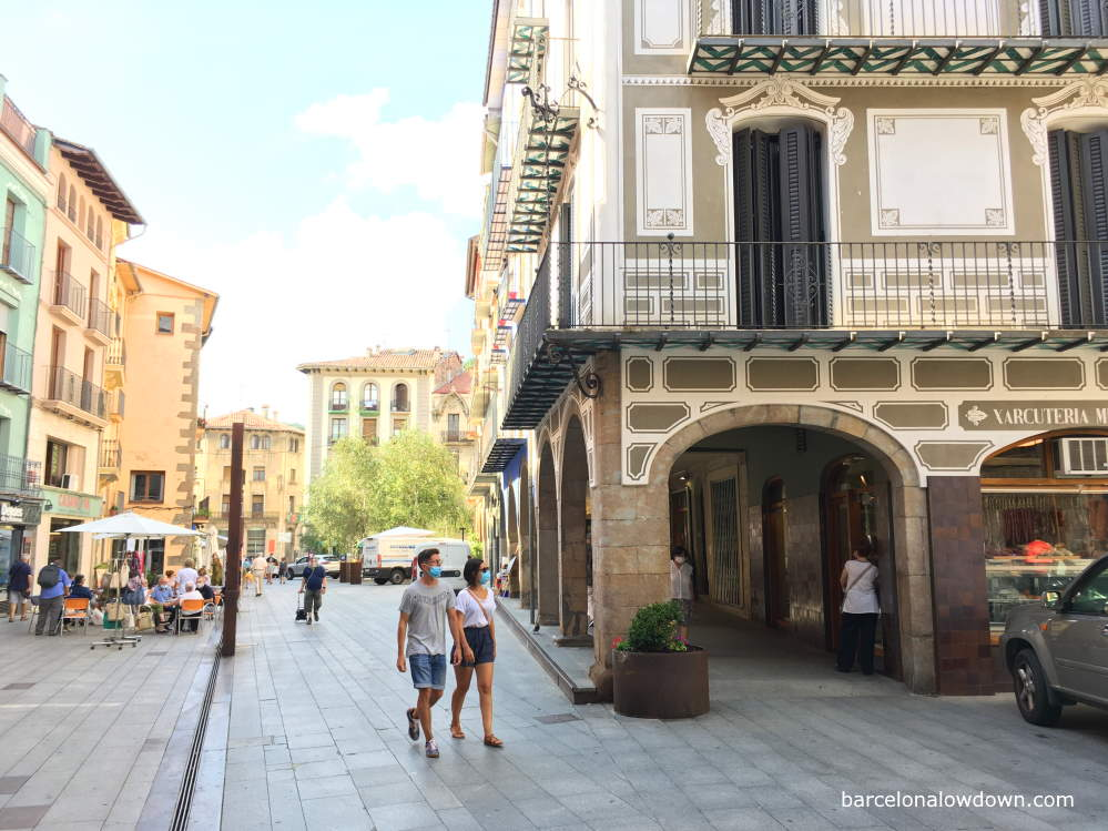 A couple walking past an old building in the centre of Ripoll, in the background there are people sitting at tables outside a bar.