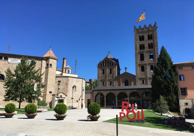 The plaza in front of the Monastery of Santa Maria de Ripoll on a sunny day. A yellow and red senyera flag flys at the top of the bell tower of the monastery.