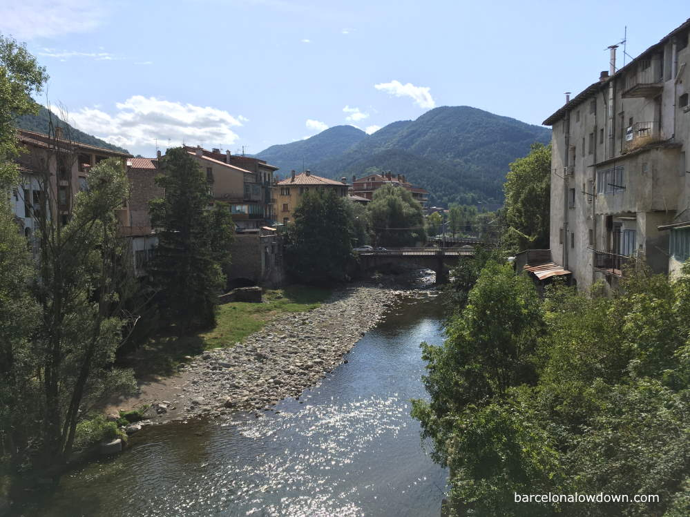 The River Freser as it passes through Ripoll with trees and old buildings either side and green mountains in the background.