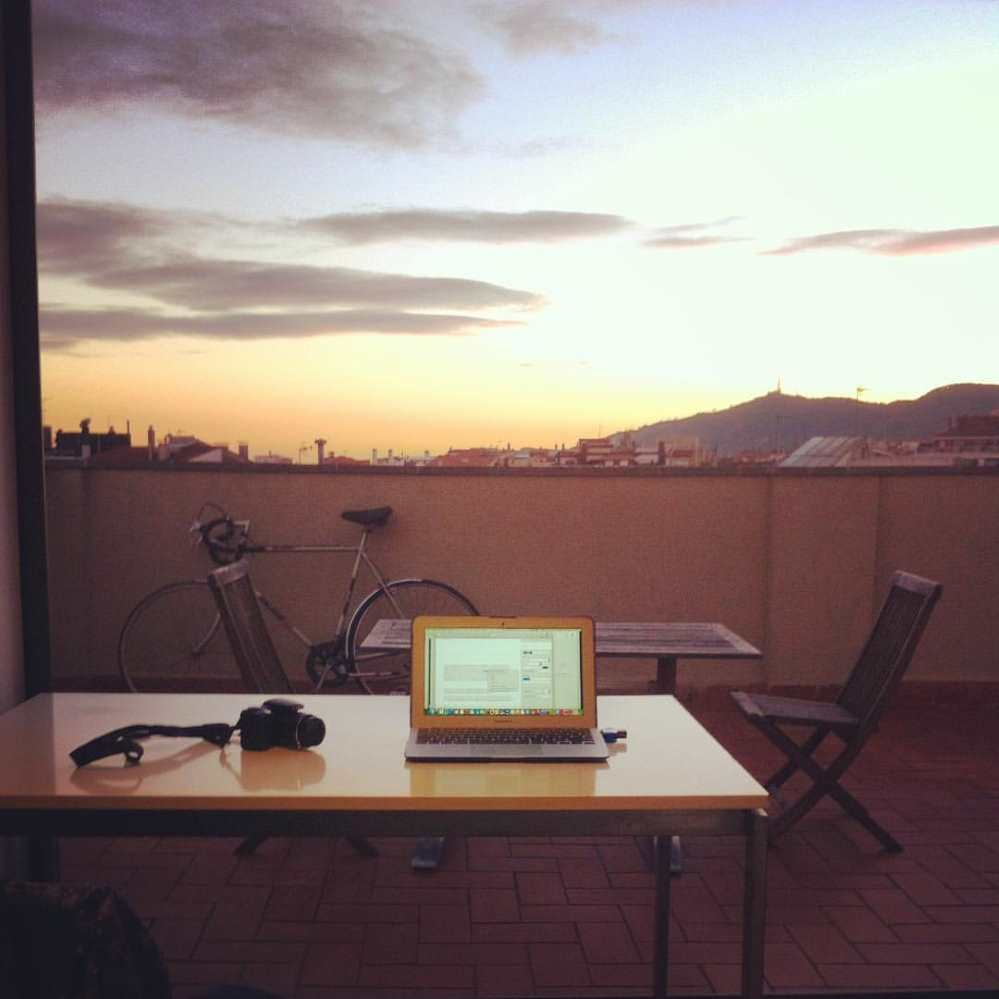 Ben Holbrook's desk on a roof terrace in Barcelona, his laptop and camera are on the desk and the sun is setting in the background