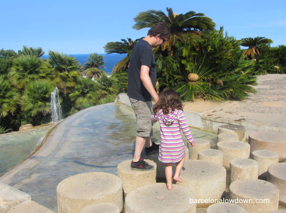 Father and child walking across stepping stones in the park near Barcelona Montjuic castle