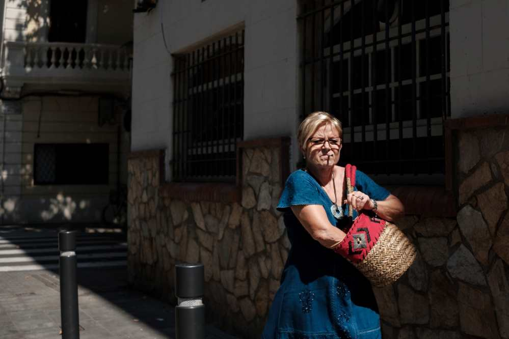 A woman in a blue dress is rummaging in her handbag looking for her lighter as she walks down a street in Barcelona - Photo by Ben Holbrook