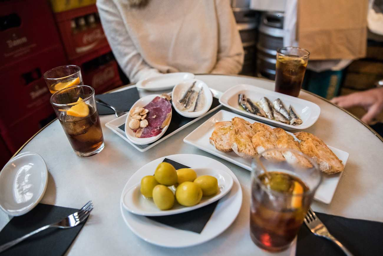 A table in a tapas bar, there are four glasses of vermouth, some olives, some bread, Spanish ham and sardines on plates