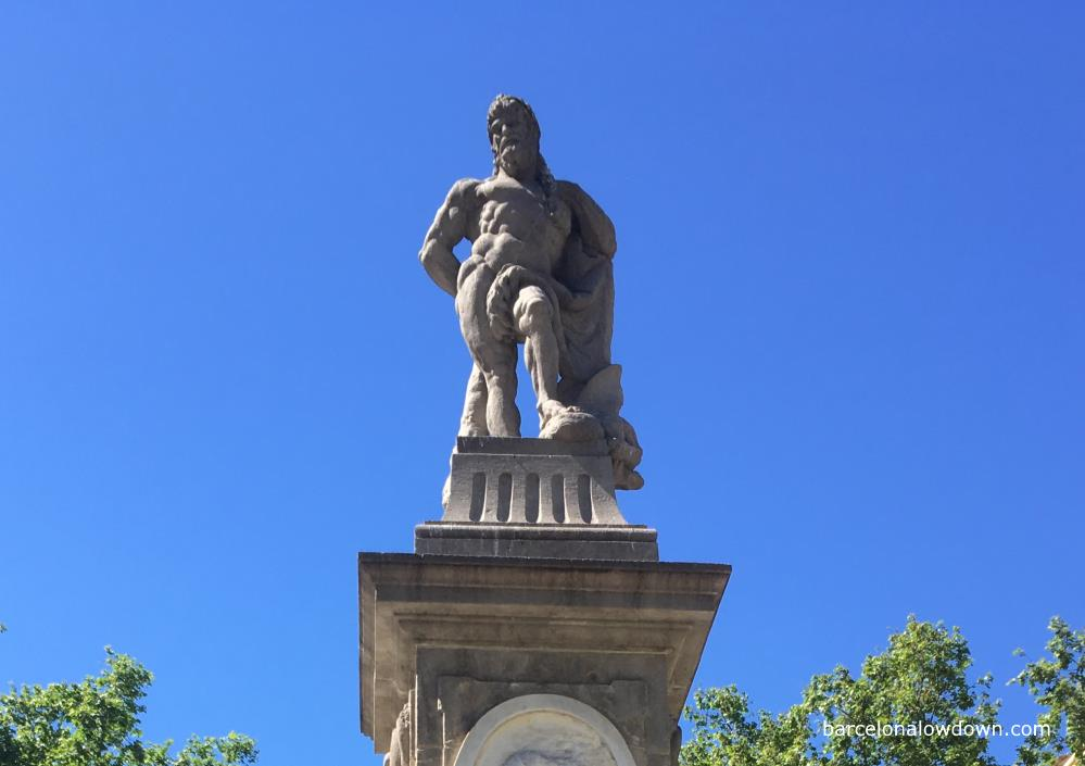 A stone statue of Hercules, standing on a pedestal with a large club in his hand