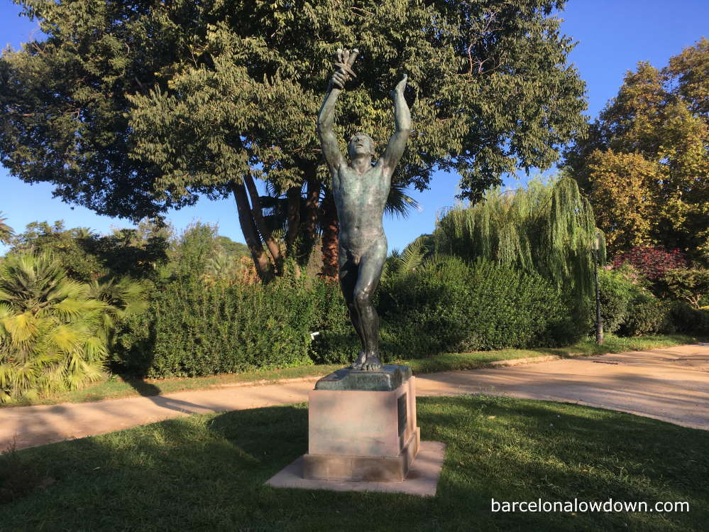 Bronze statue of a man with a dagger in a park in Barcelona