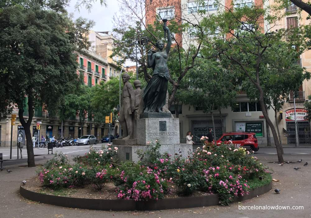 A statue in Barcelona depicting lady liberty flanked by soviet style depictions of workers