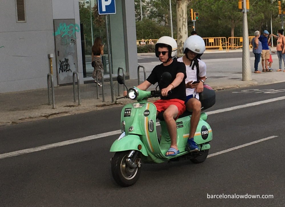 Two people riding a green electric moped in Barcelona