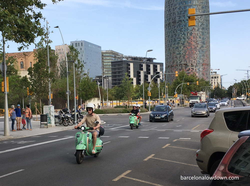 Two green electric scooters riding on the road near the Agbar Tower in Barcelona