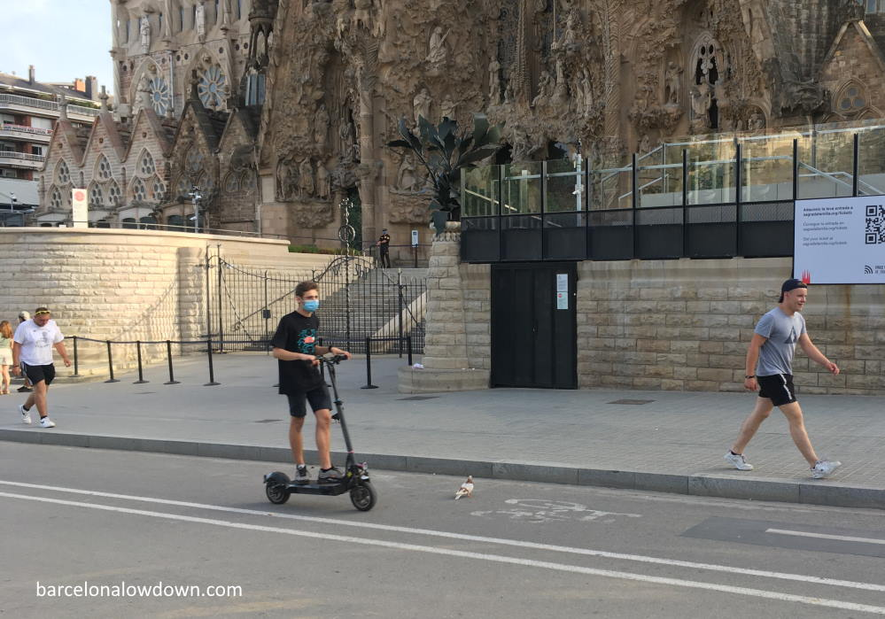 An electric scooter passing in front of the Sagrada Familia Basilica in Barcelona
