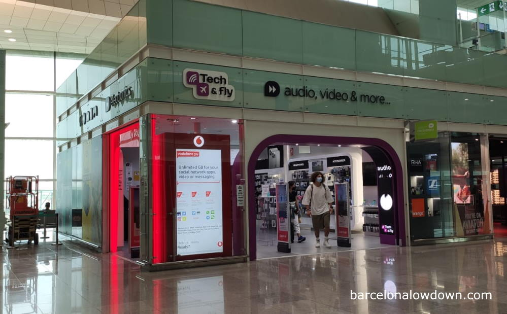 an electronics shop at Barcelona airport with a large poster advertising prepaid Spanish sim cards for mobile phones
